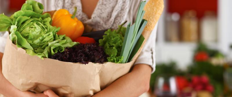 Photo of a woman holding a paper bag full of fresh vegetables.