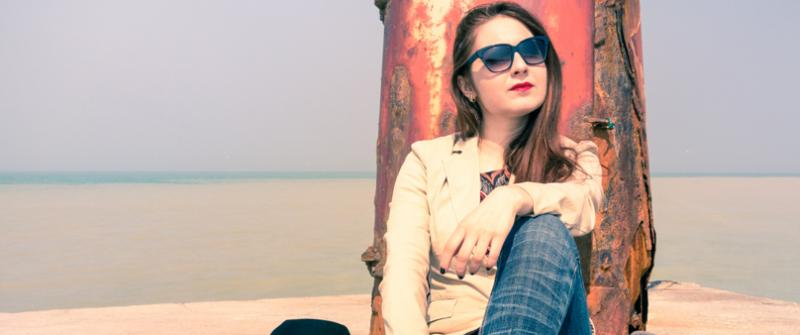 Photo of a pensive young woman leaning against a rusty post, near the ocean. She has a bag and laptop sitting next to her.