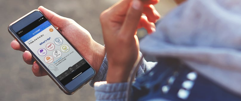 A photo of hands holding a smartphone with the Smokefree QuitSTART app on the screen.