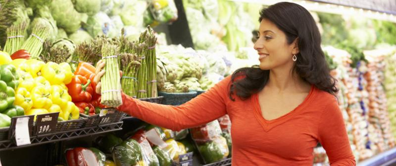 Photo of a woman picking out asparagus while standing behind her shopping cart.