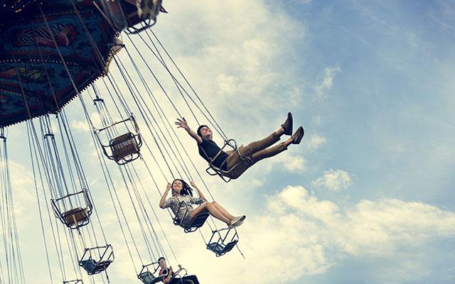 Teens having fun in carnival swings