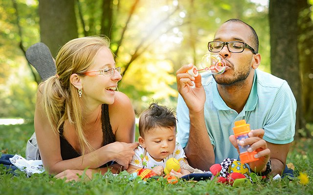 photo of a family lying on a blanket in the grass, blowing bubbles