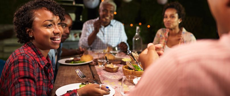 Photo of a family eating dinner together happily outside in the evening