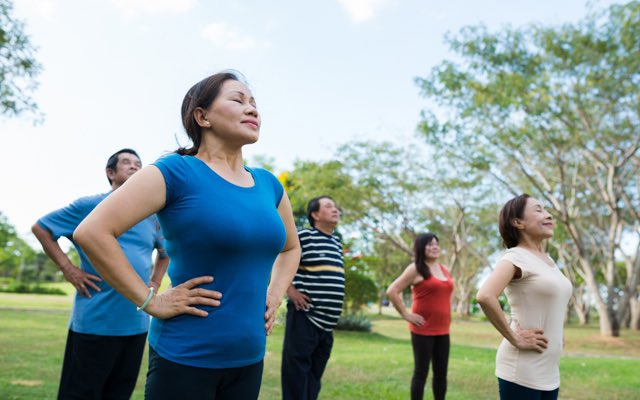 Photo of a group of adults outdoors, each striking the same yoga pose with their hands on their hips and eyes closed