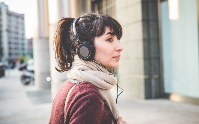 Photo of a woman walking down a city street with headphones and a scarf looks back over her shoulder