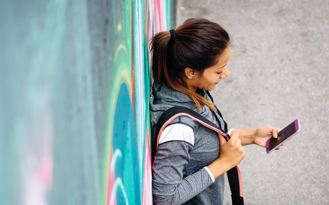 Photo of a woman leaning against a wall decorated with graffiti. She is looking at her phone.
