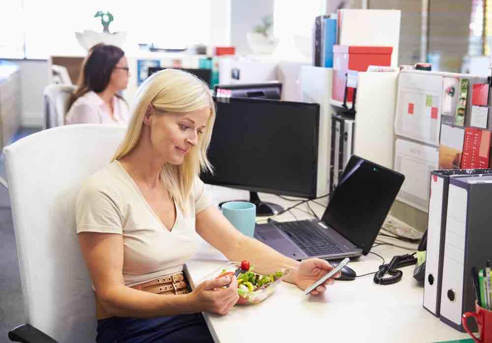 Woman looking at phone eating salad