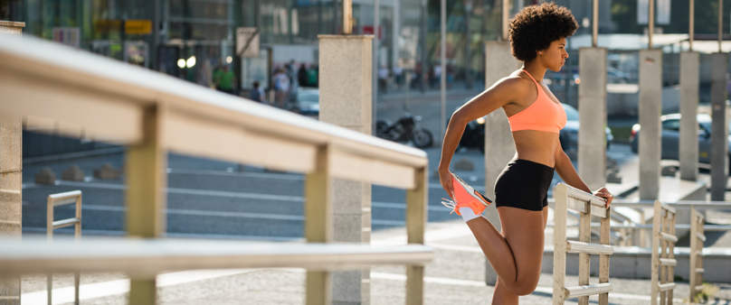 Photo of a woman in running clothes stretches while bracing herself against a handrail