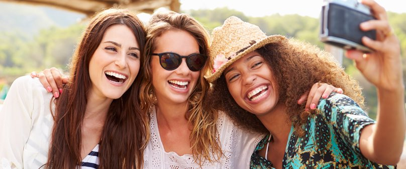 Photo of three women with their arms around one another as they lean in to take a selfie