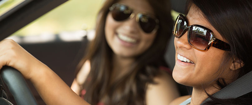 Teen girls sitting in a car wearing sunglasses