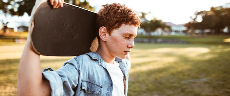 A Young man stands in a field holding a skateboard behind his head.