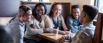 Five young people sit at a table in a restaurant, there are two coffee cups on the table.