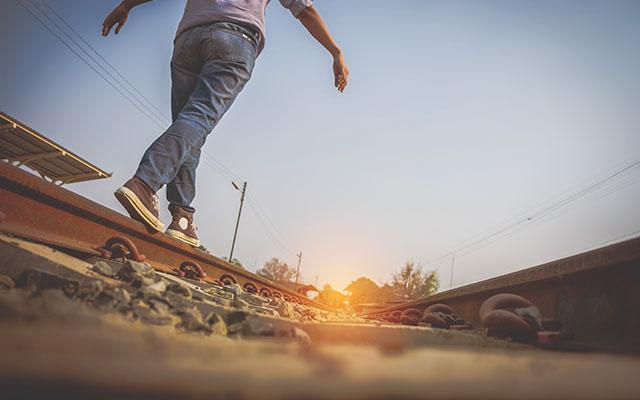 young man balancing on railroad track beam