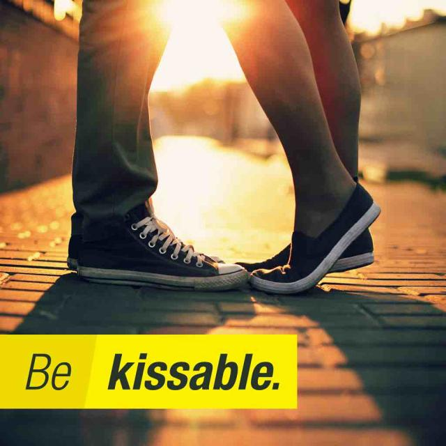 Feet and legs of two people kissing in front of sunset with text stating 'Be kissable'