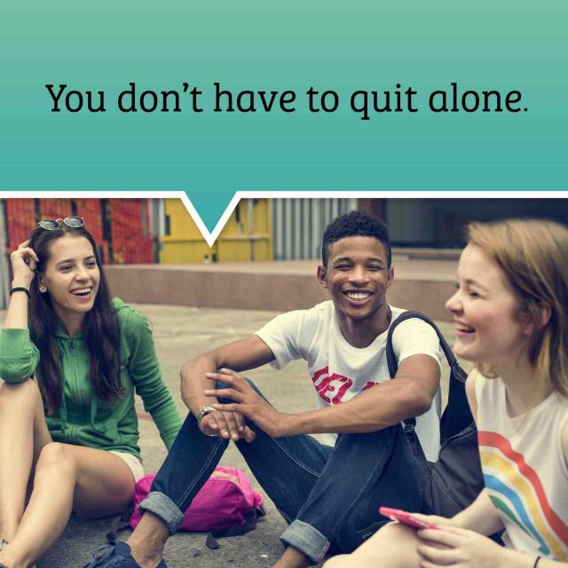 "three teens sitting on the ground talking and laughing. Text bubble above their heads saying ""you don't have to quit alone""."